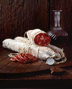 Spanish chorizo sausage on wooden chopping boardの写真素材 [FYI03542418]