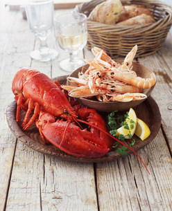 Plate of lobster and prawns with wicker basket of breadの写真素材 [FYI03542436]