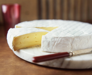 Brie round with cheese knife on marble cutting boardの写真素材 [FYI03542444]