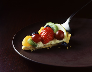 Slice of strawberry, kiwi, orange and grape tart on plateの写真素材 [FYI03542451]