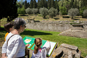 Senior woman and grandchildren looking at ruins information sign, Florence, Italyの写真素材 [FYI03542580]