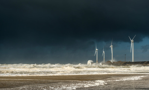 Four wind turbines amidst fierce storm waves and clouds at coast, Boulogne-sur-Mer, Nord-pas-de-Calaの写真素材 [FYI03542611]
