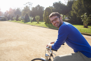 Mid adult man sitting on bicycle in park looking at camera smilingの写真素材 [FYI03542726]