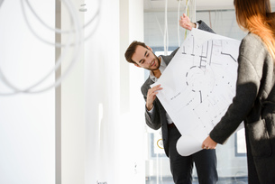 Architect showing blue print to client in new office buildingの写真素材 [FYI03542768]