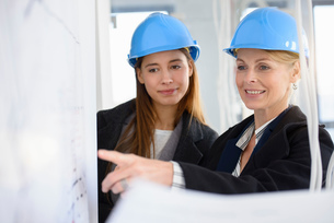Businesswoman pointing at blue print in new office buildingの写真素材 [FYI03542771]