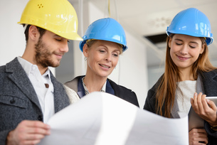 Architect looking at blue print with businesswomen in new office buildingの写真素材 [FYI03542776]