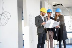 Architect explaining blue print to businesswomen in new office buildingの写真素材 [FYI03542777]