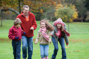Family running in park, smilingの写真素材 [FYI03542994]