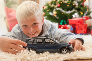 Boy lying on front holding toy car looking at camera smilingの写真素材 [FYI03543030]