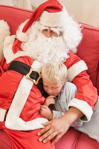 Man sitting on sofa dressed as santa hugging boyの写真素材 [FYI03543035]