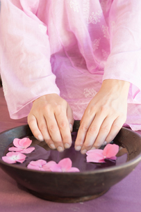 Cropped shot of young woman's fingernails soaking in bowl of flower petal water at spaの写真素材 [FYI03543080]