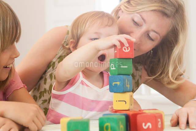 Mother and big sister watching baby girl stack building blocksの写真素材 [FYI03543104]