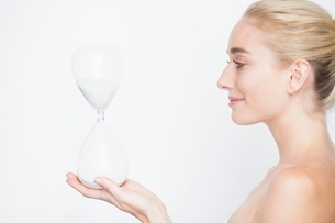 Side view of bare shouldered woman holding hourglass smilingの写真素材 [FYI03543167]