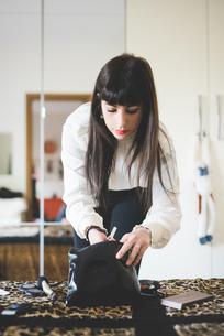 Young woman looking in makeup bag in bedroomの写真素材 [FYI03543171]