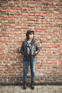 Young woman in front of brick wallの写真素材 [FYI03543195]