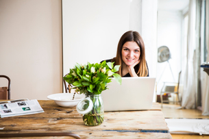 Portrait of young woman sitting at table with breakfast and laptopの写真素材 [FYI03543296]