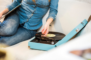 Cropped shot of young woman sitting on sofa listening to vintage record playerの写真素材 [FYI03543319]
