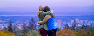 Two young women, standing on hillside, hugging, looking at view, rear viewの写真素材 [FYI03543581]