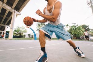 Cropped view of man on basketball court running, bouncing basketballの写真素材 [FYI03543597]