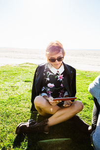 Young woman sitting cross legged on grass, looking at digital tabletの写真素材 [FYI03543634]