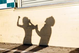 Shadow on wall of couple dancing, outdoorsの写真素材 [FYI03543654]