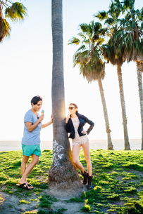 Young couple leaning against sunlit palm tree eating ice cream cones, Venice Beach, California, USAの写真素材 [FYI03543667]