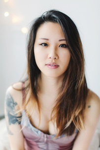 Portrait of young woman, wearing underwear, tattoo on armの写真素材 [FYI03543793]