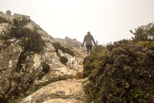 Rear view of female hiker and her dog hiking in misty mountains, Spainの写真素材 [FYI03543921]