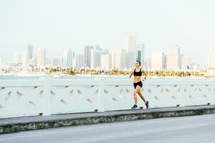 Young woman running on bridge pathwayの写真素材 [FYI03543926]