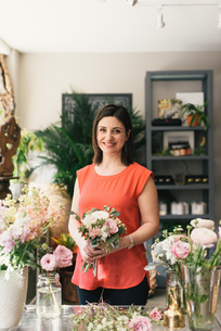 Portrait of florist in flower shop, holding bouquet, smilingの写真素材 [FYI03543998]