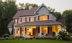 Exterior of illuminated cottage style beige stone, red trimmed home with gardenの写真素材 [FYI03544078]