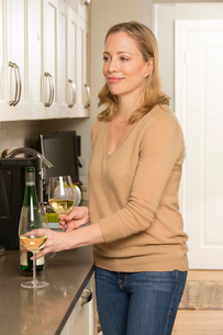 Woman with glasses of white wine at kitchen counterの写真素材 [FYI03544106]