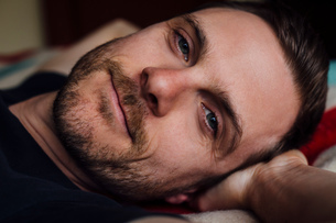 Close up portrait of handsome confident man on bed with hands behind headの写真素材 [FYI03544125]