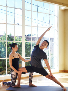 Man and woman doing yoga in studio, woman supporting man in reverse warrior positionの写真素材 [FYI03544218]
