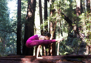 Mid adult woman doing yoga in forest, in firefly poseの写真素材 [FYI03544228]