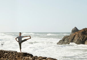 Mature man doing yoga on rocks beside ocean, extended hand to big toe poseの写真素材 [FYI03544232]