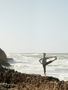 Mature man doing yoga on rocks beside ocean, extended hand to big toe poseの写真素材 [FYI03544237]