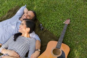 High angle view of couple lying on grass with acoustic guitar smilingの写真素材 [FYI03544380]