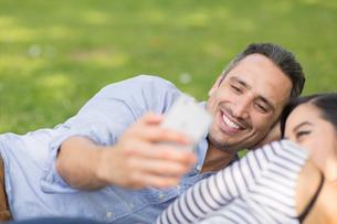 Couple lying on grass using smartphone to take selfieの写真素材 [FYI03544389]