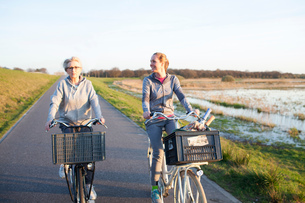 Front view of women cycling on path by marshland smilingの写真素材 [FYI03544601]