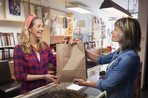 Shop assistant handing shopper shopping bagの写真素材 [FYI03544633]