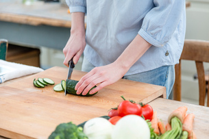 Mid section of woman slicing cucumberの写真素材 [FYI03544692]