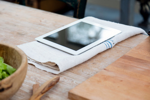Digital tablet on tea towel on wooden surfaceの写真素材 [FYI03544693]