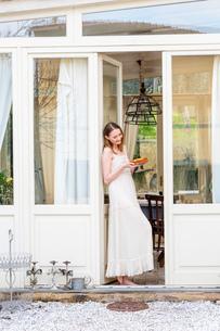 Woman standing in doorway holding cakeの写真素材 [FYI03544704]