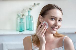 Woman moisturising face with cotton wool padの写真素材 [FYI03544737]
