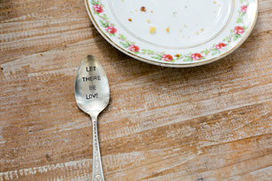 Plate and spoon engraved with slogan on wooden surfaceの写真素材 [FYI03544747]