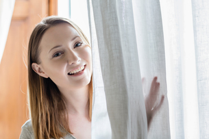 Portrait of woman peeking from behind curtain looking at camera smilingの写真素材 [FYI03544767]