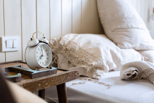 Unmade bed, alarm clock on bedside tableの写真素材 [FYI03544769]