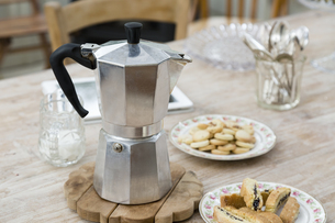Stove top coffee pot with plates of baked good on dining tableの写真素材 [FYI03544778]