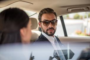 Young businessman and woman talking in car backseat, Dubai, United Arab Emiratesの写真素材 [FYI03544882]